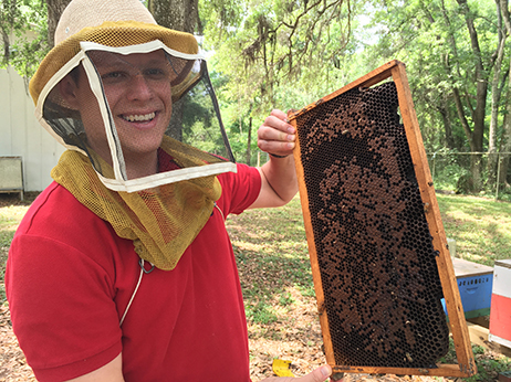 Cameron Jack holding bee frame